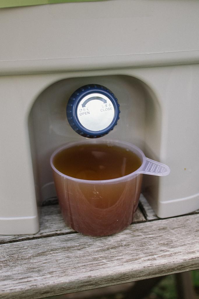 Ein Plastikbecher voll mit Bokashi-Saft unter dem Auslasshahn eines Bokashi-Eimers.
